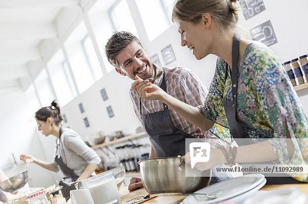 Couple enjoying cooking class kitchen
