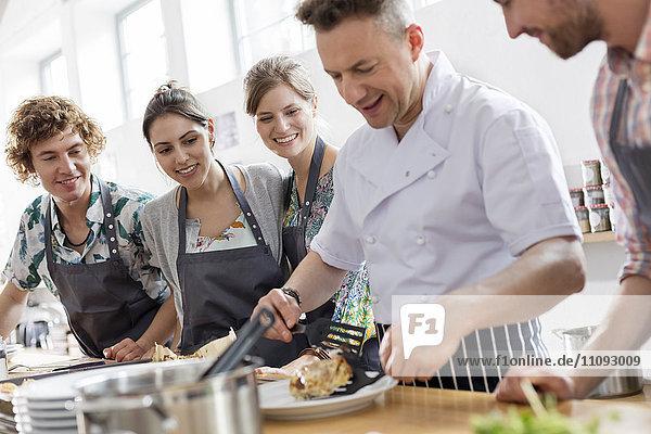 Schüler beobachten Kochlehrer in der Küche des Kochkurses