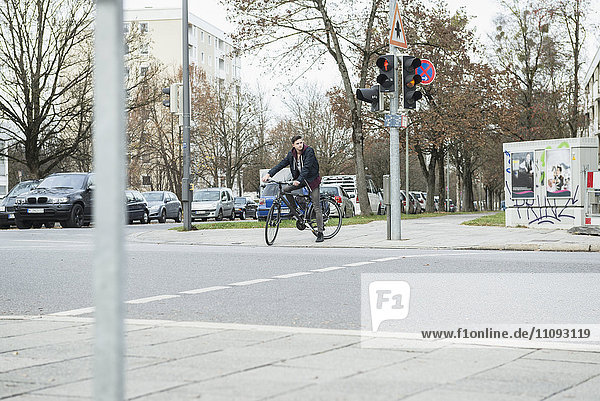 Young man with bicycle in the city waiting by the red traffic light