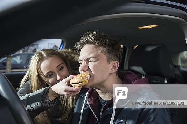 Young couple sitting in a car and she is feeding him a burger