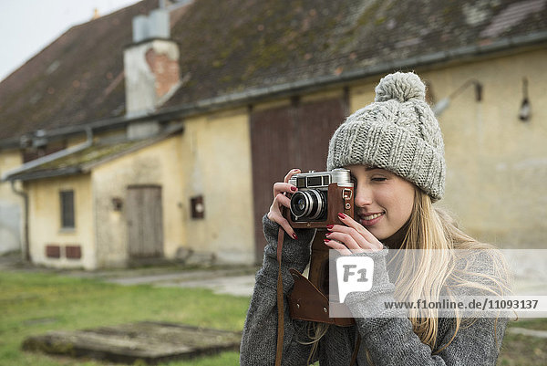 Teenage girl clicking pictures with retro styled camera