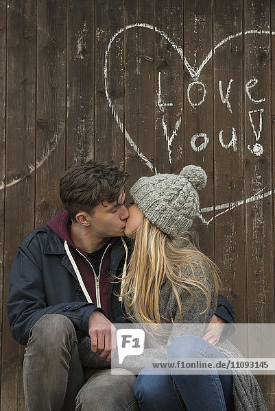 Young couple kissing with a drawn heart and love you written on a wooden wall