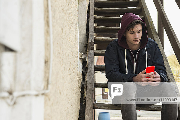 Young man text messaging on smart phone and sitting on wooden stairs