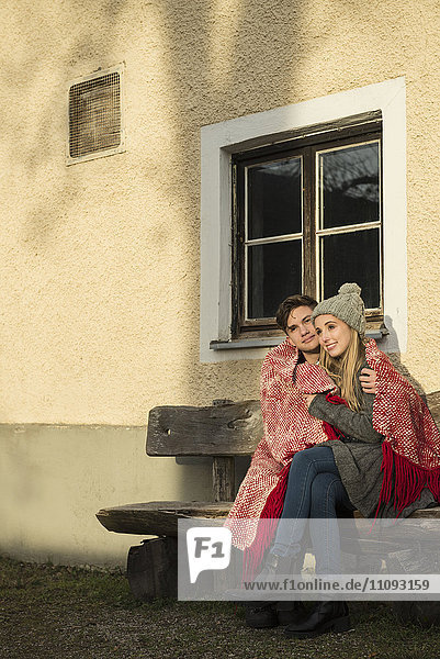 Young couple wrapped in a blanket sitting on bench during sunset