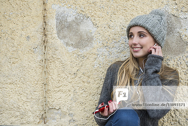 Teenage girl listening to music on mobile phone and leaning against wall