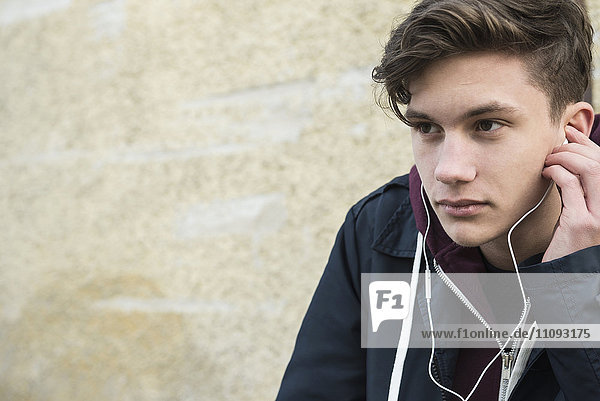 Close-up of young man listening to music with earbud