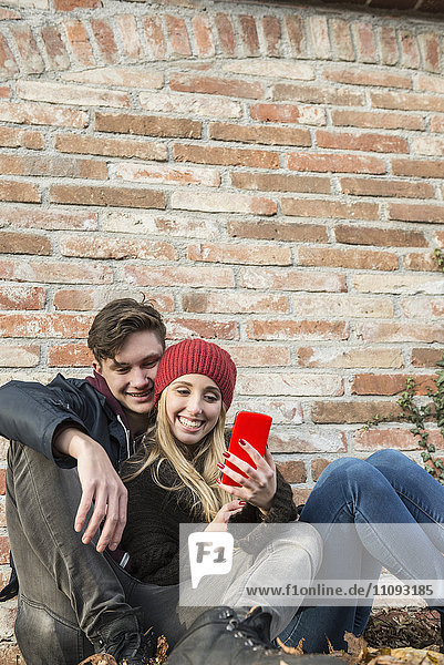 Young couple smiling and using smart phone against brick wall