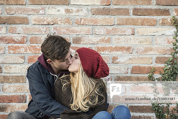 Young couple kissing against brick wall