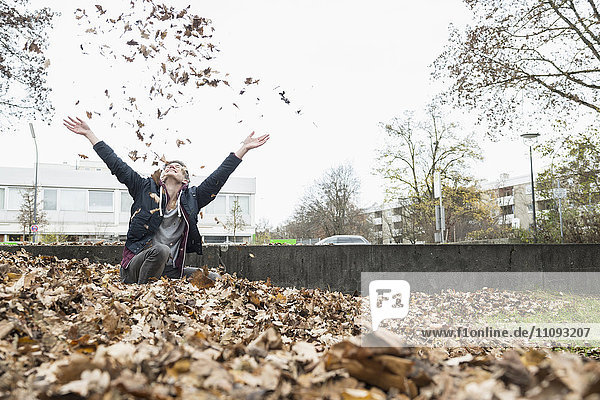 Young man throwing autumn dry leaves in air