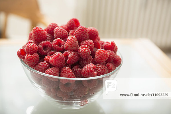 Raspberries in glass bowl on table