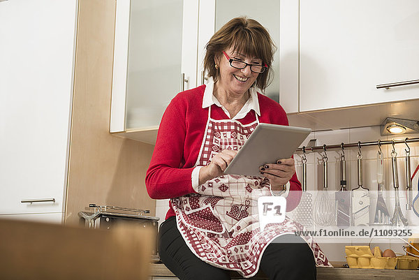 Senior woman wearing apron in the kitchen and reading digital tablet
