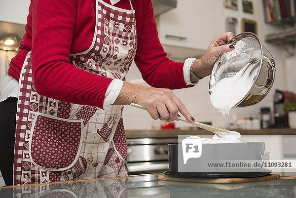 Senior woman pouring meringue on cake base in springform pan
