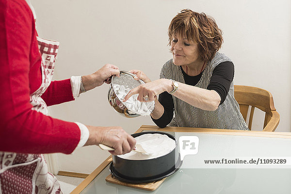 Senior woman nibbling meringue with finger in kitchen Senior woman nibbling meringue with finger in kitchen