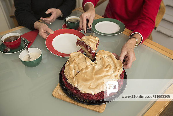 Senior woman cutting a piece of meringue cake and Serving to her old friend
