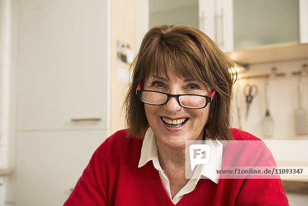 Portrait of a senior woman sitting in the kitchen and smiling