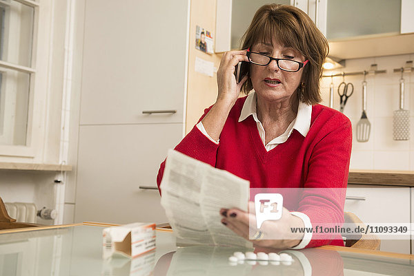 Senior woman reading package insert for pills and talking on phone