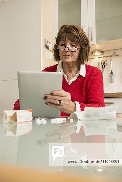 Senior woman reading package insert for pills on digital tablet