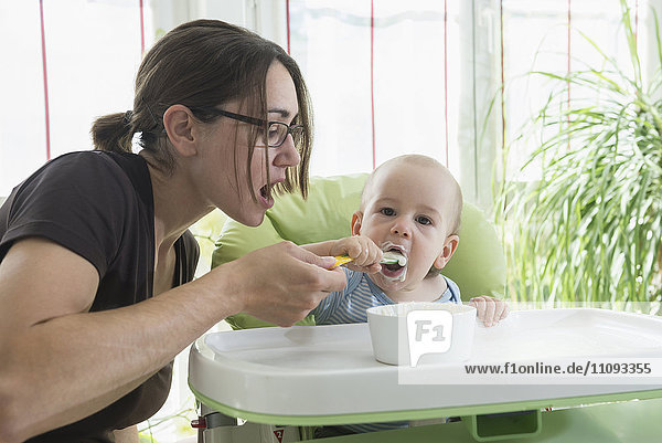 Mother feeding baby food to her baby boy with spoon  Munich  Bavaria  Germany Mother feeding baby food to her baby boy with spoon, Munich, Bavaria, Germany