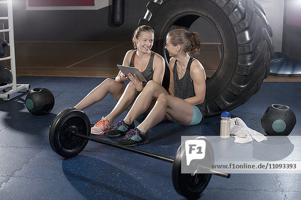 Two women relaxing and using digital tablet after exercise