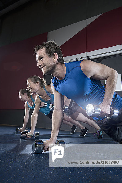 Athletes doing push ups in the gym by holding dumbbell