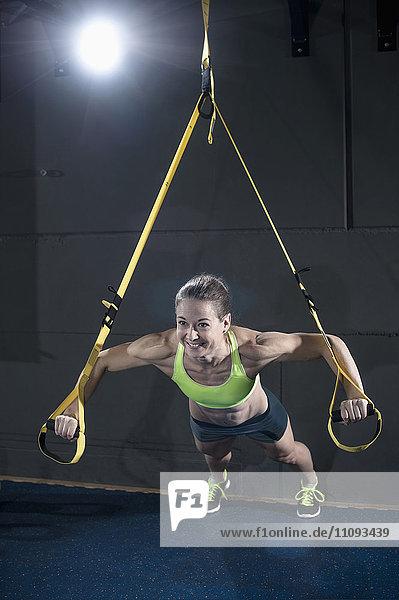 Sportive woman doing press-ups with TRX belt in health club Sportive woman doing press-ups with TRX belt in health club