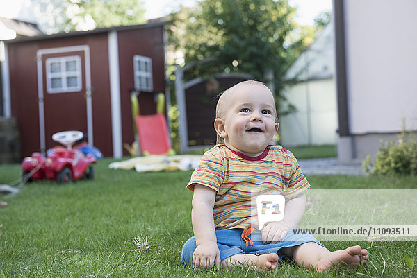 Little cute baby boy sitting on grass and laughing in a lawn  Munich  Bavaria  Germany Little cute baby boy sitting on grass and laughing in a lawn, Munich, Bavaria, Germany