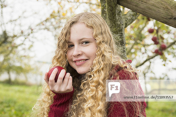 Portrait of a blond teenage girl eating an apple in an apple orchard farm