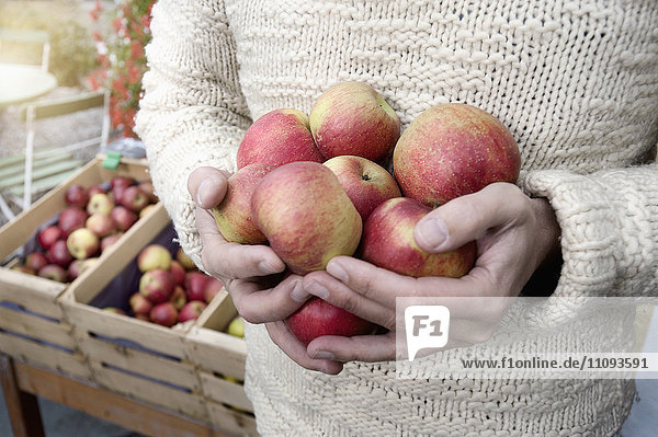 Mid section of a man holding apples in his hands in front of wholefood shop