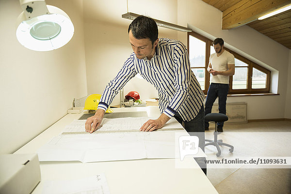 Architect working on blueprint in office  Bavaria  Germany