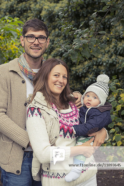 Portrait of a nuclear family standing in an organic farm and smiling