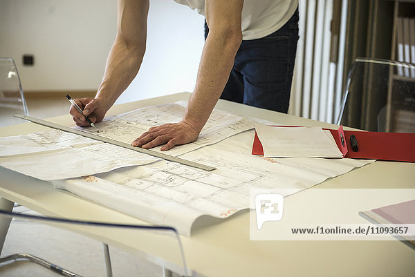 Midsection view of an architect making a blueprint in the office  Bavaria  Germany