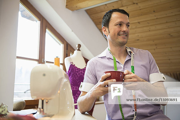 Male dressmaker having a cup of coffee with sewing machine  Bavaria  Germany