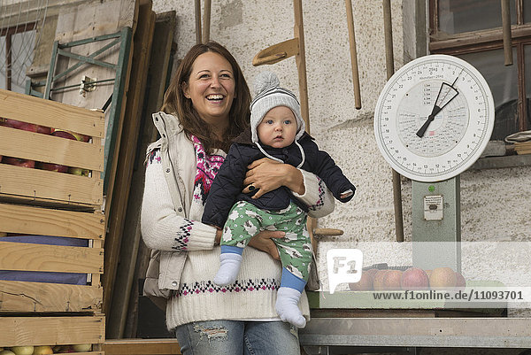 Organic farmer woman with her baby son standing in farm and scale in the background