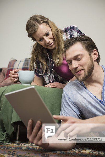 Couple using digital tablet in living room and smiling  Munich  Bavaria  Germany