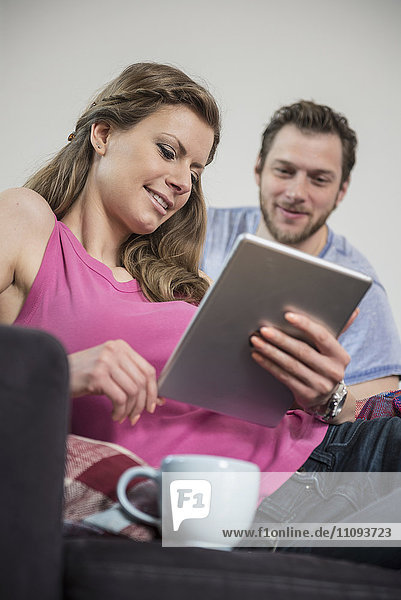 Couple using digital tablet in living room  Munich  Bavaria  Germany