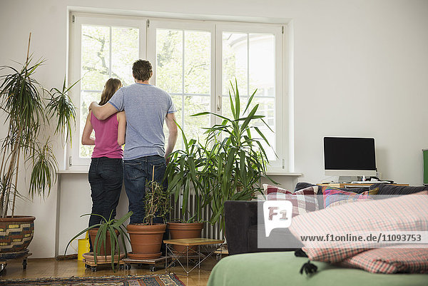 Rear view of a couple standing in living room and looking through window  Munich  Bavaria  Germany