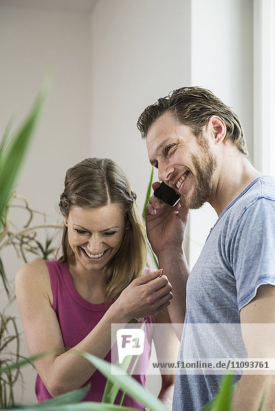 Mid adult man talking on mobile phone in living room and smiling  Munich  Bavaria  Germany