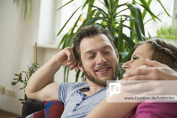 Couple resting on sofa in living room and looking at each other  Munich  Bavaria  Germany