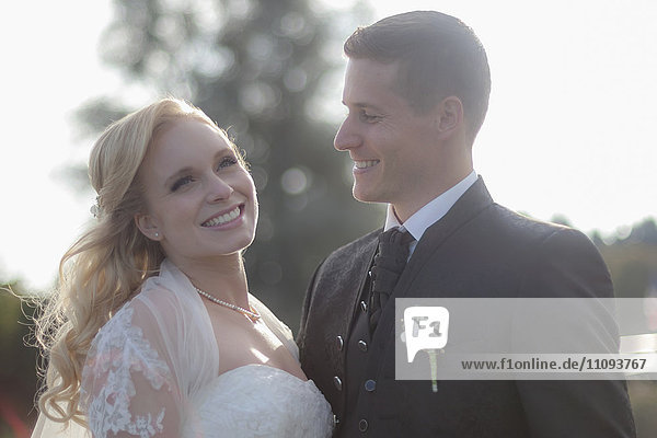 Close-up of a bride and groom smiling