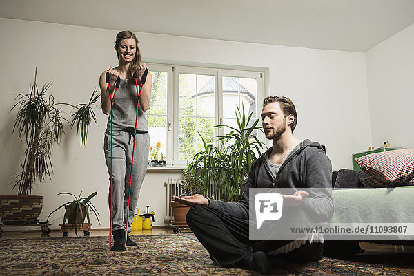 Couple doing exercise in living room  Munich  Bavaria  Germany