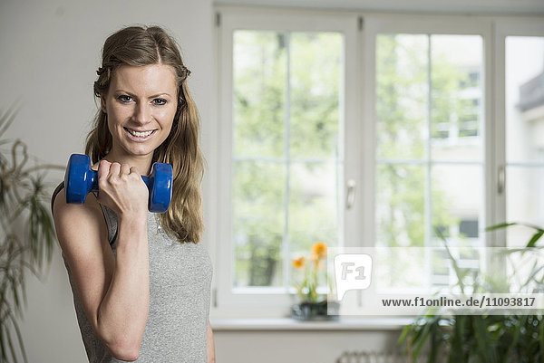Young woman doing exercise with dumbbell in living room and smiling  Munich  Bavaria  Germany