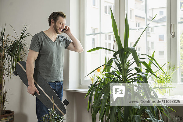Mid adult man talking on mobile phone in living room  Munich  Bavaria  Germany
