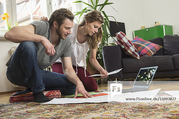 Couple looking at map in living room  Munich  Bavaria  Germany Couple looking at map in living room, Munich, Bavaria, Germany