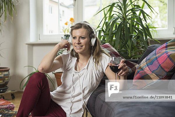 Young woman listening to music and drinking wine in living room  Munich  Bavaria