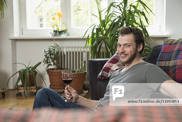Mid adult man drinking red wine in living room and smiling  Munich  Bavaria  Germany