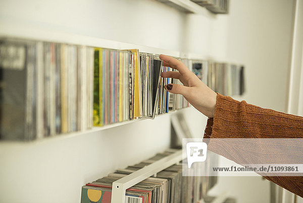Close-up of a woman hand picking a cd from shelf  Munich  Bavaria  Germany Close-up of a woman hand picking a cd from shelf, Munich, Bavaria, Germany