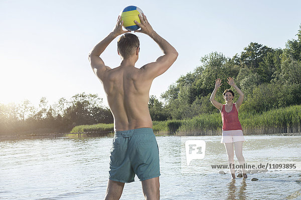 Mature couple playing volleyball at the lake  Bavaria  Germany