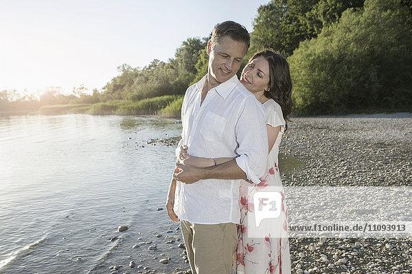 Mature couple romancing at lakeside and smiling  Bavaria  Germany