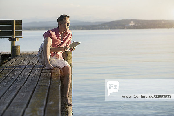 Mature man using digital tablet on pier and looking over lake  Bavaria  Germany Mature man using digital tablet on pier and looking over lake, Bavaria, Germany