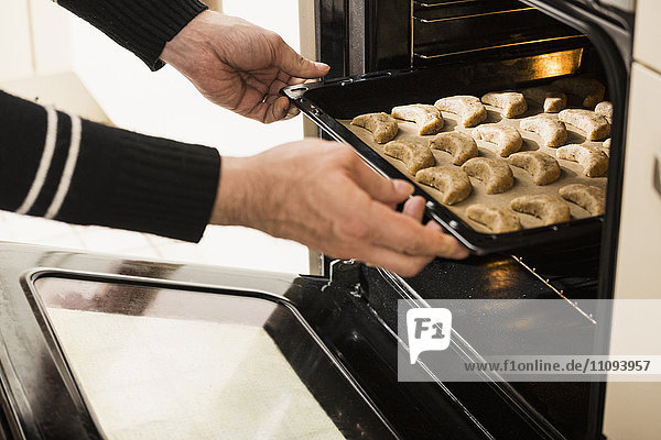Close-up of a man putting baking tray of vanilla crescents in oven for baking